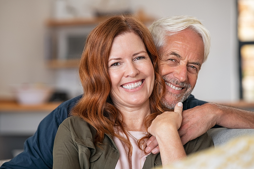 Portrait of middle aged couple hugging and looking at camera. Cl